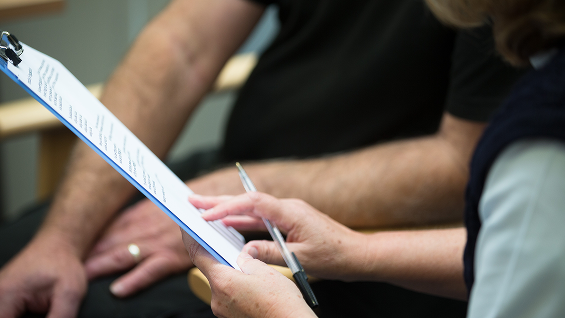 Close up of research nurses hands pointing at clipboard