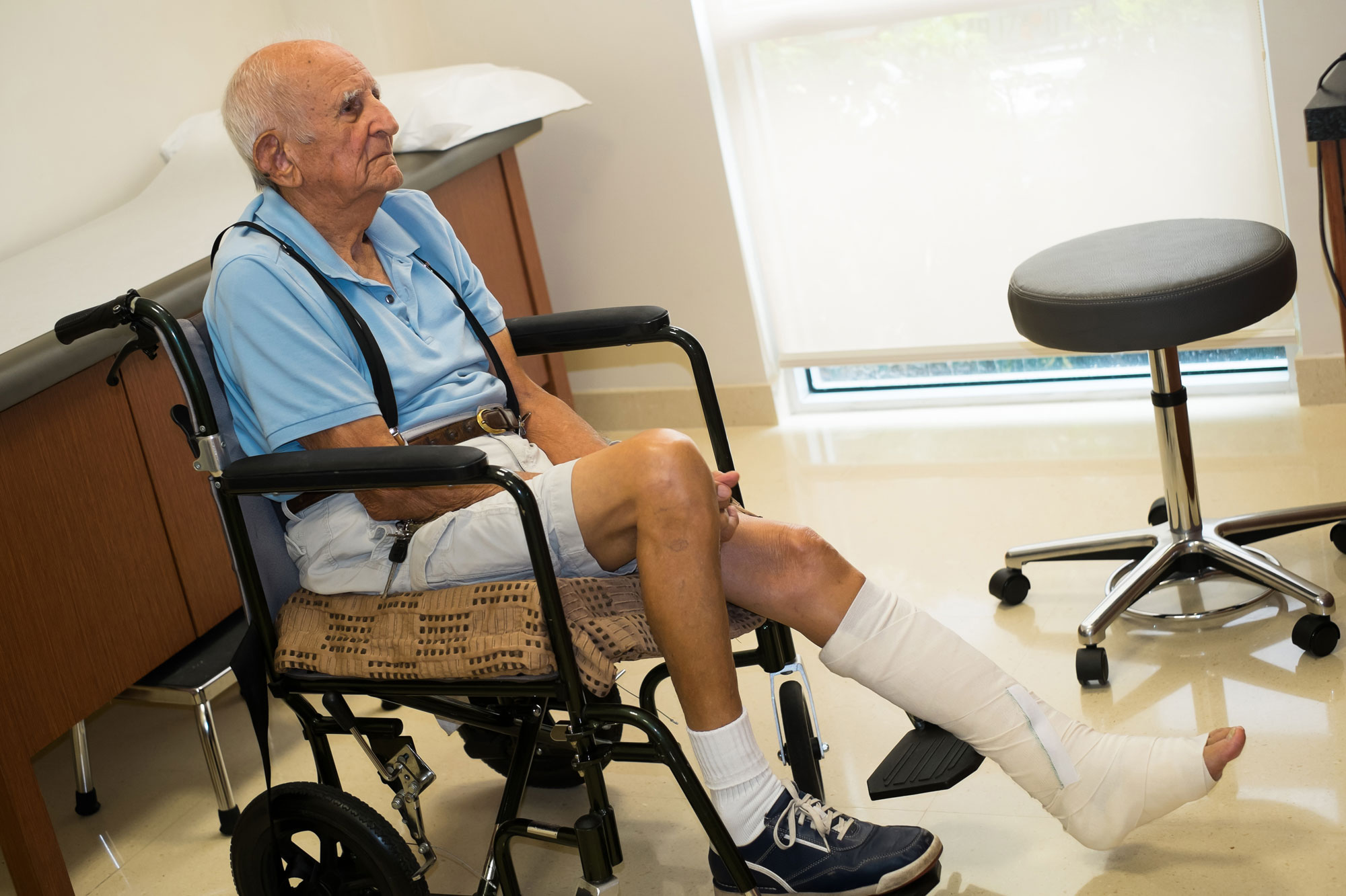 Elderly man sitting in a wheelchair in a clinical setting.