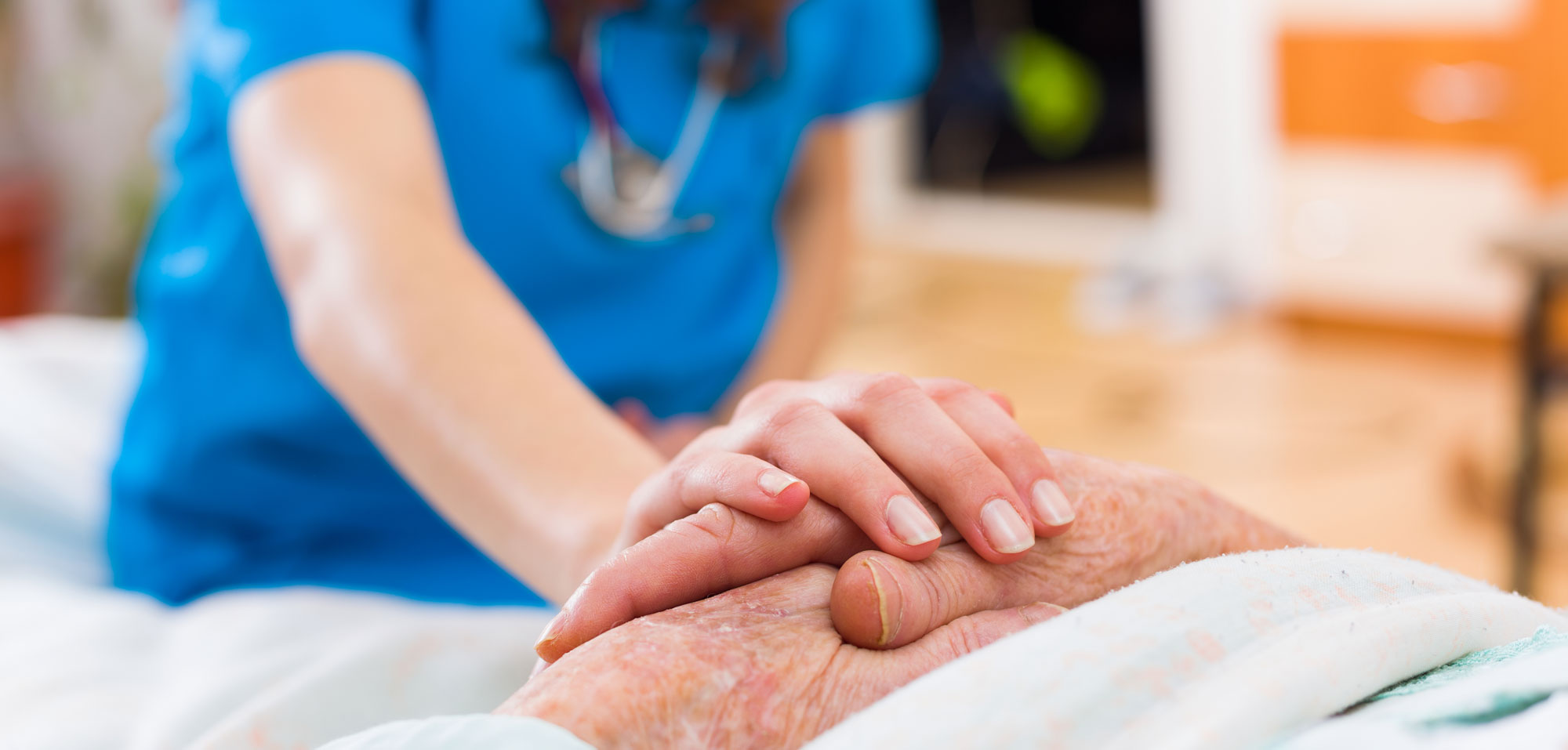 Nurse holds the hand of an elderly woman in a hospital setting.