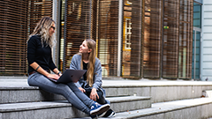 Two students sit on some steps talking to each other